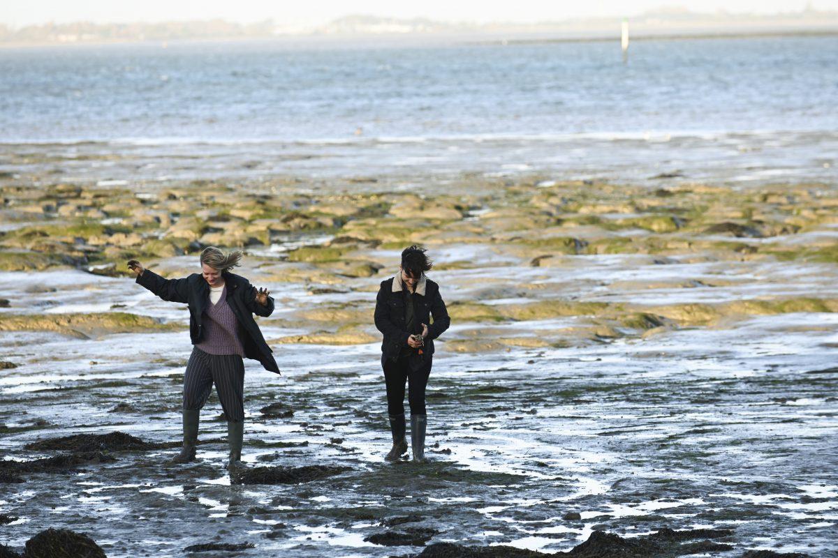 Anna (Mia Wasikowska) und ihre Partnerin Chris (Bex Taylor-Klaus) am Strand beim waten durch das Wattenmeer