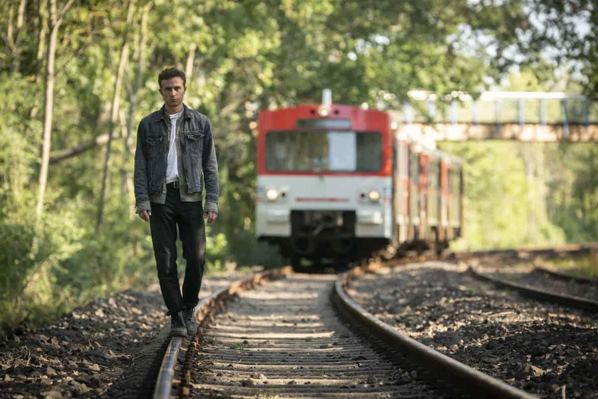 Max Hubacher balanciert auf einem Gleis. Ein Zug kommt hinter ihm angefahren