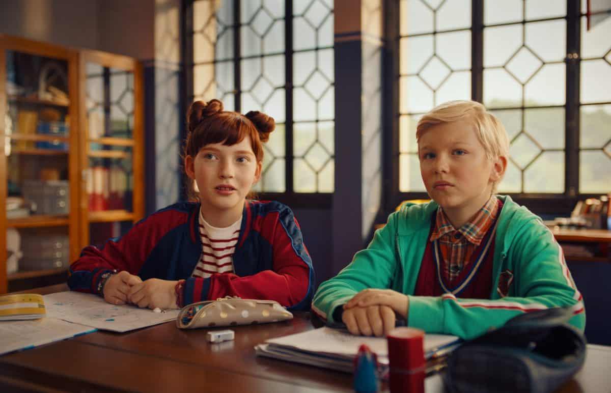 Benni (Leonard Conrads) bekommt mit Ida (Emilia Maier) eine neue Sitznachbarin in der Klasse. Szenefoto zum kommenden Film Die Schule der magischen Tiere
