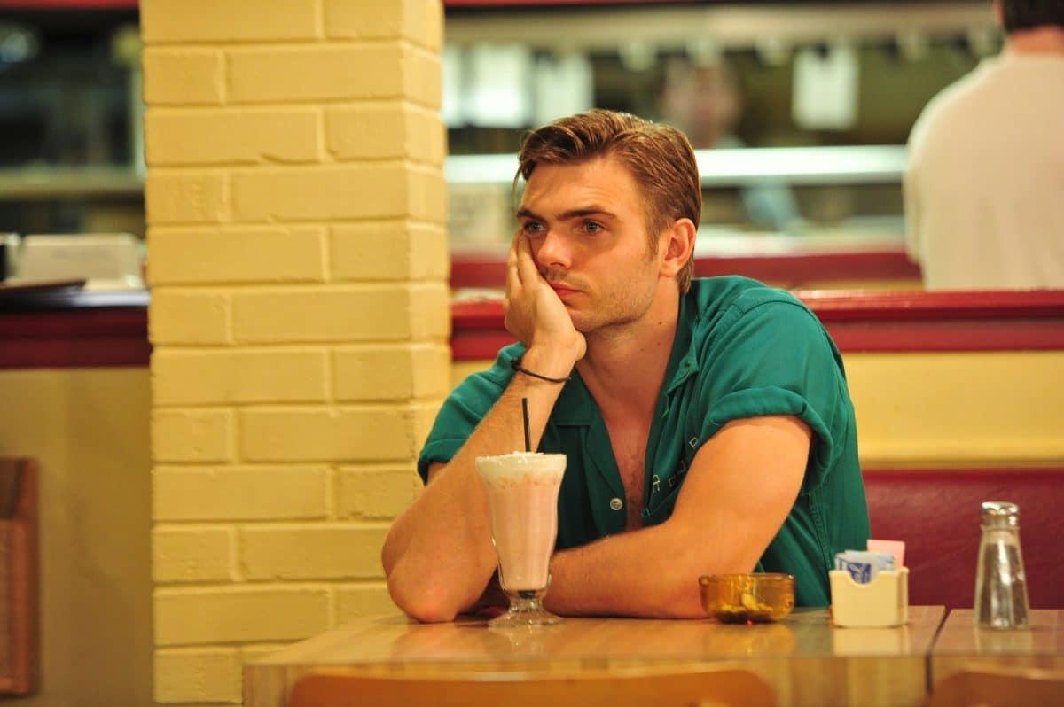 Einsamer Junge sitzt in einem Cafeim Film Hot Summer Nights