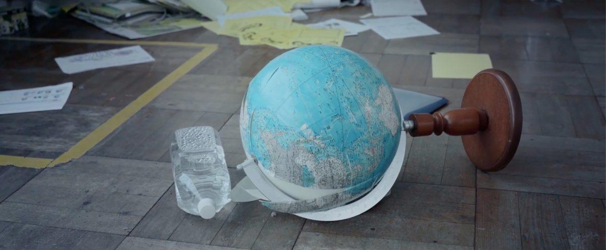 Eine Plastikflsche liegt neben einem umgekippten Globus auf dem Boden. Im Hintergrund sind Blätter und Papiere zu sehen